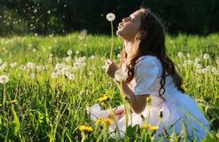 Teen blowing seeds from a dandelion flower in a spring park. A teen blowing seeds from a dandelion flower in a spring park Royalty Free Stock Image