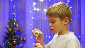 Teen blowing soap bubbles at home. In the background, bokeh lights and garlands. stock video