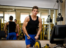 Teen bodybuilder exercising pecs muscles with gym equipment. Teen bodybuilder working out with gym equipment, exercising pecs muscles with cables Stock Images