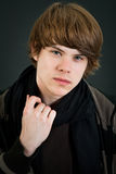 Teen boy. Handsome teen male holding his scarf over dark background Royalty Free Stock Photos