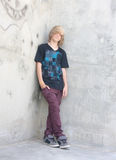 Teen Boy. Cute teen boy with long shaggy hair standing against a cement wall with graffiti Stock Images