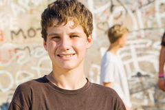 Teen boy. Young teen boy holding a skateboard with friends in the background Stock Photography