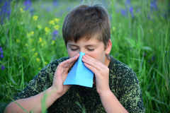 Teen boy with allergies in flowering herbs Stock Photography