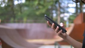 Teen boy alone using a mobile phone against the background of a skate park. while other children are actively relaxing stock video footage