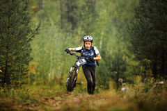 Teen boy athlete mountainbike uphill on foot with his bicycle stock images