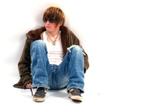 Teen Boy with Attitude. Teenage boy sitting down with sunglasses and an attitude Stock Photo