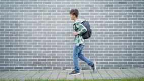Teen boy back to school. Teen boy with backpack go to school moves on street next to an Brick Wall. Cute child teenager with bag Back to School. Concepts of stock video