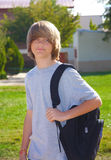 Teen boy with Backpack. Teen boy standing in front of a school carrying a backpack Royalty Free Stock Photos