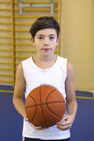 Teen boy with basketball ball in gym Stock Image