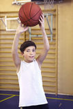 Teen boy with basketball ball in gym Royalty Free Stock Photos