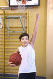 Teen boy with basketball ball in gym Royalty Free Stock Images
