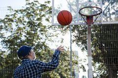 Teen boy basketball player in action in a basketball court stock photo