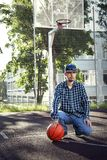 Teen boy basketball player with ball outdoors royalty free stock images