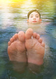Teen boy bathing in sea close up photo. Teen boy bathing swimming feet out in sea close up photo Stock Image