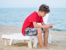 Teen boy on beach. Side view of teen boy using a smart phone on the beach. Teenager texting on the cellphone on sea - outdoors in summer Royalty Free Stock Photo