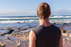 Teen Boy Beach Waves. Teen boy unidentified standing on beach morning watching looking at ocean waves and reefs stock photos