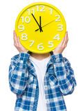 Teen boy with big clock. Caucasian teen boy covered his face with clock. Funny teenager showing yellow clock. Child back to school, isolated on white background Royalty Free Stock Photos