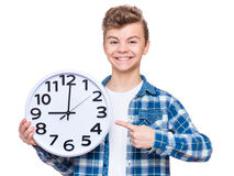 Teen boy with big clock. Portrait of caucasian teen boy with clock. Funny teenager showing clock, looking at camera. Child back to school, isolated on white Royalty Free Stock Photos