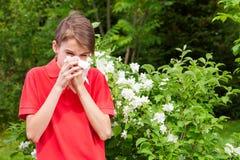 Teen boy blowing his nose on a tissue in a spring garden seasonal infection concept stock photography