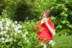 Teen boy blowing his nose on a tissue in a spring garden seasonal infection concept royalty free stock photos