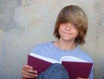 Teen Boy with Book. Cute teen boy sitting against a cement wall reading a book Stock Photography