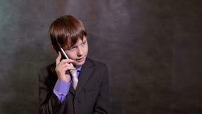 Teen boy businessman talking on the phone stock footage