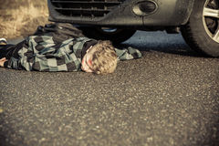 Teen Boy Car Accident Victim Lying on Road by Car Royalty Free Stock Photos