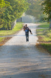 Teen boy carry teen girl on road Stock Images