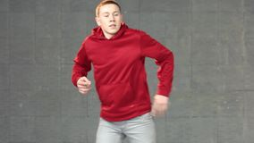 Teen boy in casual outfit dancing modern dance. Caucasian guy in red sweater performing hip-hop in studio. Lesson of contemporary dance stock video