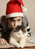Teen boy with cat in christmas santa hat royalty free stock photo