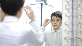 Teen boy is choosing new eyeglasses in optics. Teen boy selects points in front of the mirror optics stock video footage