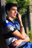 Teen Boy Communication. A closeup view of a typical teen boy with dark hair, relaxed and happily talking on a cellphone. Shallow depth of field Royalty Free Stock Images