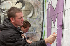 Teen boy concentrating on painting graffiti Stock Images
