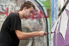 Teen boy concentrating on painting graffiti Stock Image