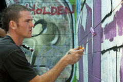Teen boy concentrating on painting graffiti Royalty Free Stock Image