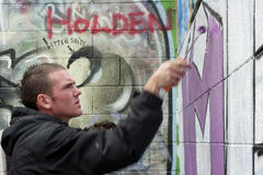 Teen boy concentrating on painting graffiti Royalty Free Stock Images