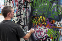 Teen boy concentrating on painting graffiti Royalty Free Stock Photos