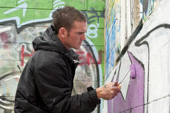 Teen boy concentrating on painting graffiti Stock Photography