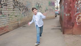 Teen boy dancing, street dancing on the background of brick wall