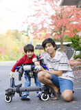 Teen boy with disabled little brother in walker. Out walking Royalty Free Stock Photography