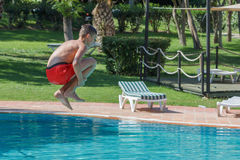 Teen boy dives and swims in the pool. On a summer day rest Stock Photo