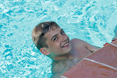 Teen boy dives and swims in the pool. On a summer day rest Royalty Free Stock Photography