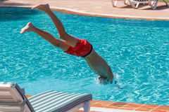 Teen boy dives and swims in the pool. On a summer day rest Stock Images