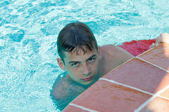 Teen boy dives and swims in the pool. On a summer day rest Stock Photos