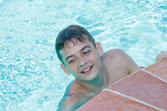 Teen boy dives and swims in the pool. On a summer day rest Royalty Free Stock Photo
