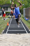 Teen Boy Doing Long Jump at Track and Field Meet Royalty Free Stock Photos