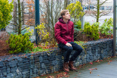 Teen boy dreaming about future ideas, visions and plans expecting good future sitting outdoor in city park. Teenager boy waiting outdoor in park on city street stock photography