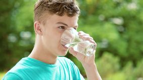 Teen boy drinking water outdoors stock video