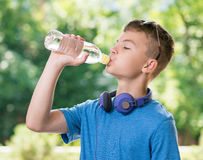 Teen boy drinking water. Teen boy 12-14 year old drinking fresh water from a bottle. Student teenager with headphones and sunglasses posing outdoors stock photography