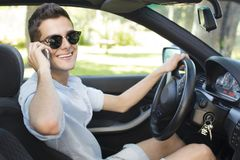Teen boy driving car and talking on phone. A teenage boy behind the wheel of a car and talking in a mobile phone Royalty Free Stock Images